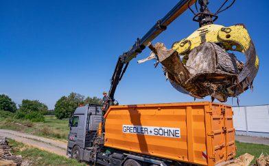 Container Lkw mit Kran lädt Holzstämme auf.